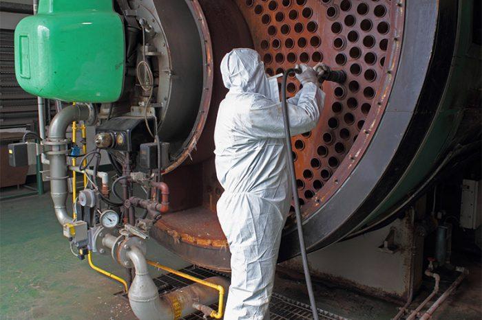 Arbeiter reinigt Maschine